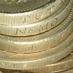 Pile of pound coins - by Ian Britton (FreeFoto.com)