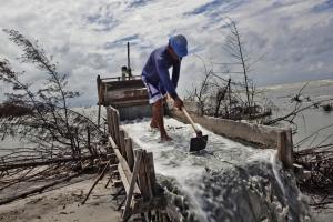 Edi, a sea tin miner, separates sand from tin ore in Rebu Village